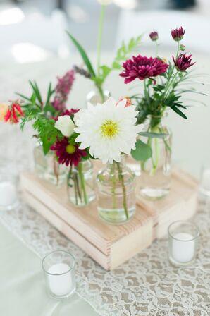 Assortment of Glass Vase Flower Arrangements on Wood Crates