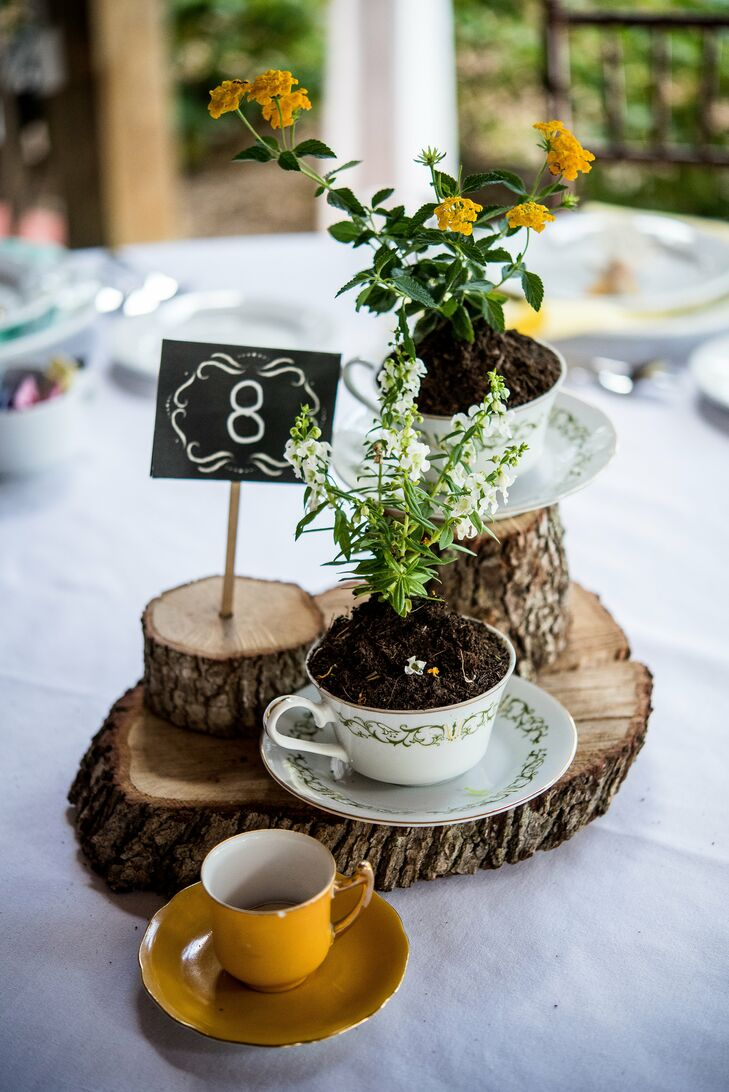 Nothing says rustic like natural-wood centerpieces. For their reception at Buckingham Farms in Fort Myers, Florida, each table was paired with three wooden stands below these potted yellow and white wildflowers in vintage teacups. A DIY black-and-white table number directed guests to their seats. (After the wedding, Angela's sister, Alyson, made the head table's centerpiece into chic candles.)