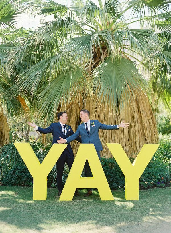 """Couple posing in front of giant yellow """"yay"""" sign"""