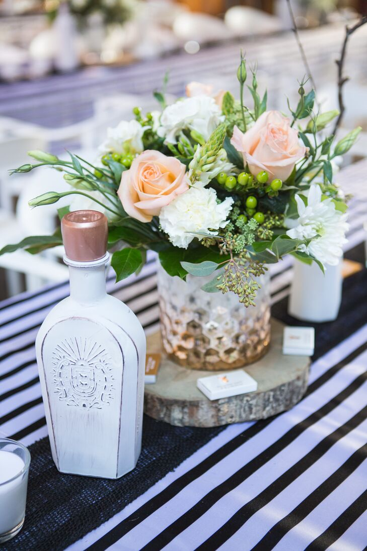 A peach rose and white carnation centerpiece was placed on a slab of wood, surrounded by white painted bottles.