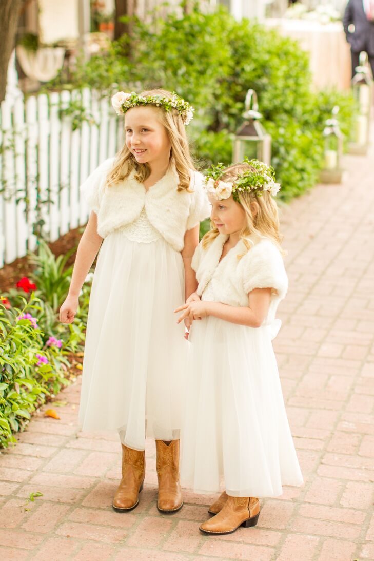 The flower girls wore mid-length, white tulle dresses, fur shawls, and forest-green flower crowns.