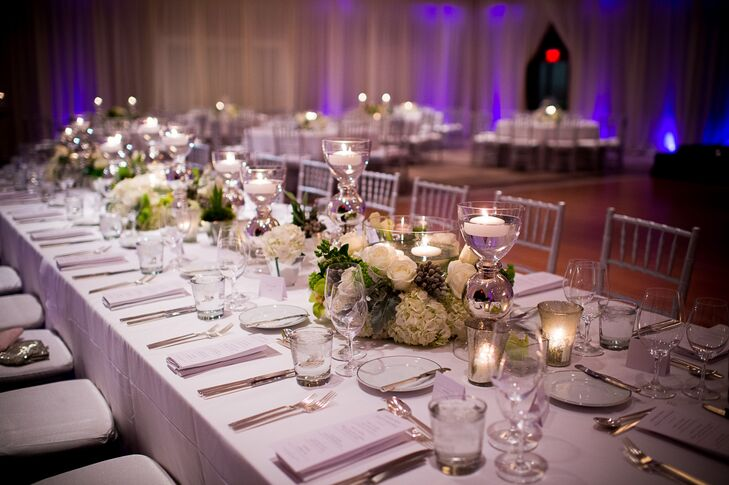 The reception table centerpieces looked wintry and glam. Each arrangement was made up of white hydrangeas, roses, orchids, calla lilies, dusty miller and silver brunia and then accented with floating candles and mercury glass.