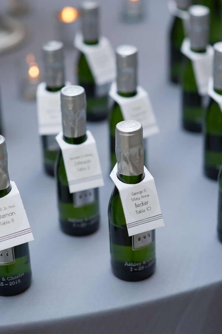 As guests entered the Roundhouse in Beacon, New York, for the reception, they were greeted by a display of pint-size champagne bottles styled alongside flickering candlelight and a towering arrangement of ivory and purple blooms. Tying into their vintage theme, an art deco-inspired escort card was attached to each bottle, guiding guests to their seats.
