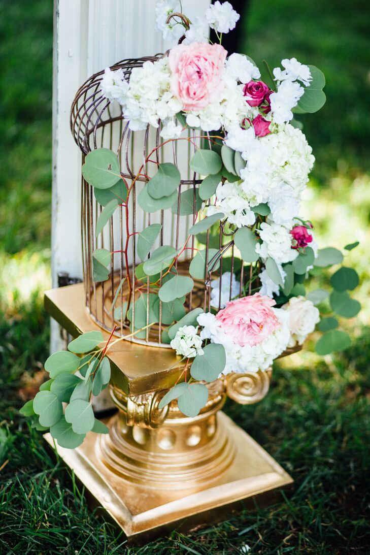 Vintage-inspired birdcages displayed atop gilded columns were adorned with cascades of eucalyptus, pink roses and fragrant white florals. They framed the vintage hearth that served as the backdrop for the ceremony. The fanciful touch played up the occasion's secret garden theme, while creating a focal point for the ceremony.
