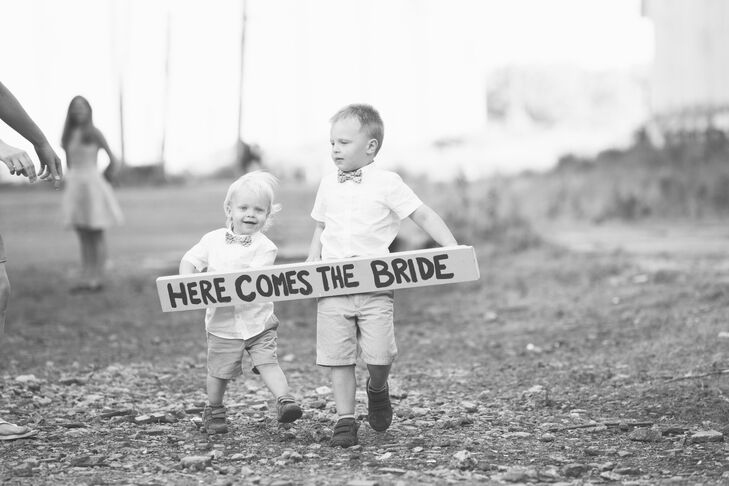 "The ring bearers announced the bride with a DIY wooden sign that said ""here comes the bride."""