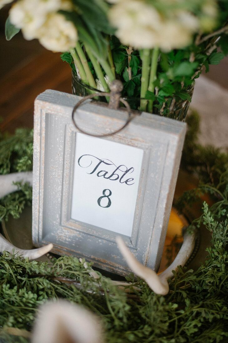The table numbers were hand calligraphed and placed in distressed wooden frames.