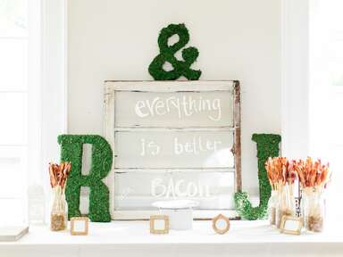Styled bacon bar with moss-covered initials