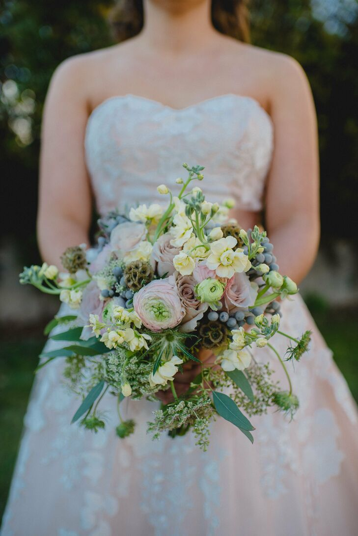 Her bouquet looked like it was just picked from a forest. Blooms filled the arrangement with pink ranunculus, mauve and light pink roses, yellow delphiniums, silver brunia, seeded eucalyptus, Queen Anne's lace, thistles and scabiosa pods for a totally natural look. The best part: Both a piece of her mother's and Charley's mother's wedding dresses was wrapped around the bouquet. Brooklee's great-great-grandmother's blue brooch fastened the fabrics together.