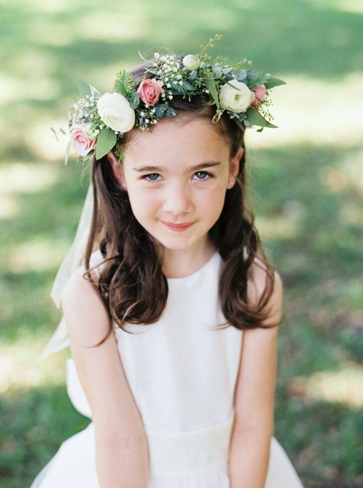 This flower girl didn't just carry natural blooms, she wore them! Her white tea-length dress was paired with a sweet flower crown filled with white ranunculus, pink roses and eucalyptus from Missy Gunnels Flowers.