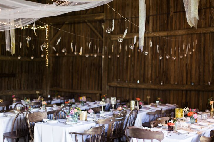 Candles stood out atop white linen-draped tables, while bistro lights, lanterns and chandeliers illuminated the barn.
