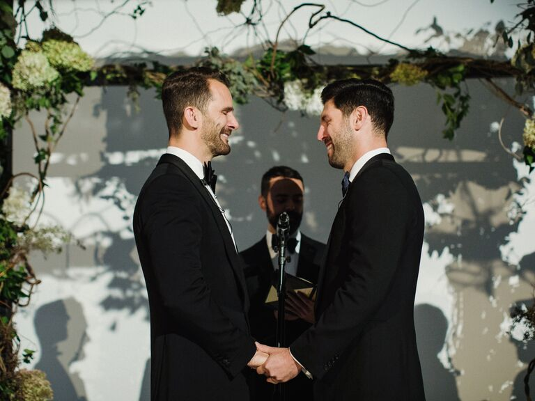 Grooms holding hands smiling