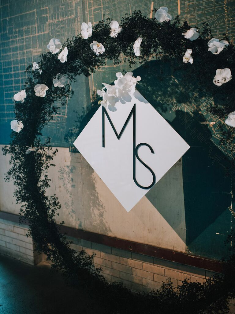 Round floral ceremony arch with white orchids and sleek monogram sign