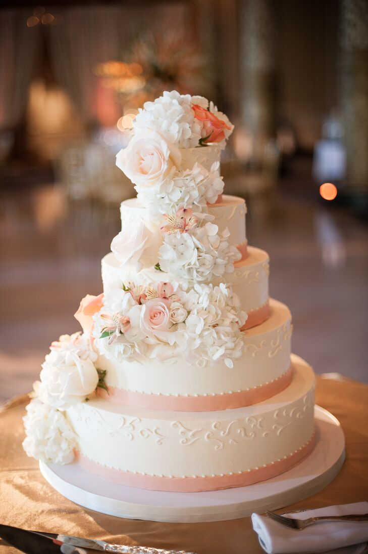 Amy Beck Cake Design created a five-tier white cake for the reception. It was decorated with piping, peach ribbon and cascading roses and hydrangeas.