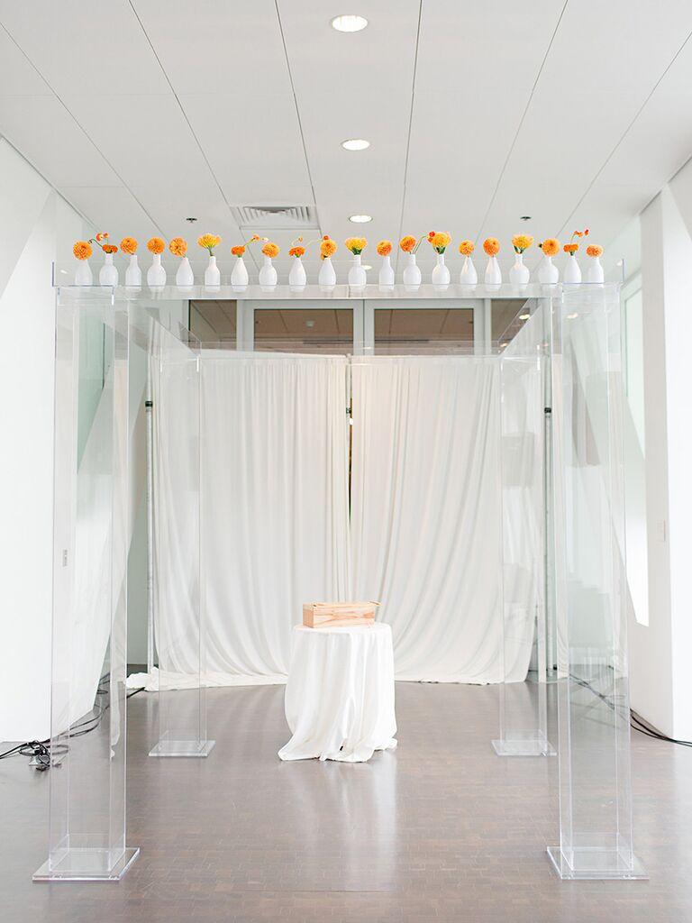 Modern wedding ceremony decor with orange flowers in bud vases