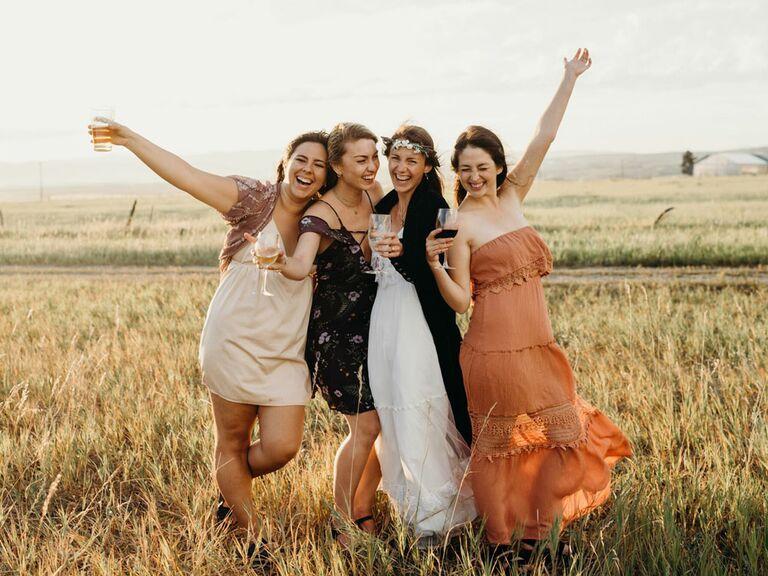 Bride posing with guests in semi-formal wedding attire at outdoor reception