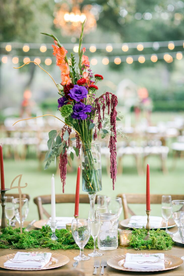 The colorful centerpieces comprised two-tone anemone dahlias in purple and orange hues, zinnias and pompom dahlias in variations of bold oranges and reds, soft hues of lilac waxflowers, and white coffee beans for added texture and shape.