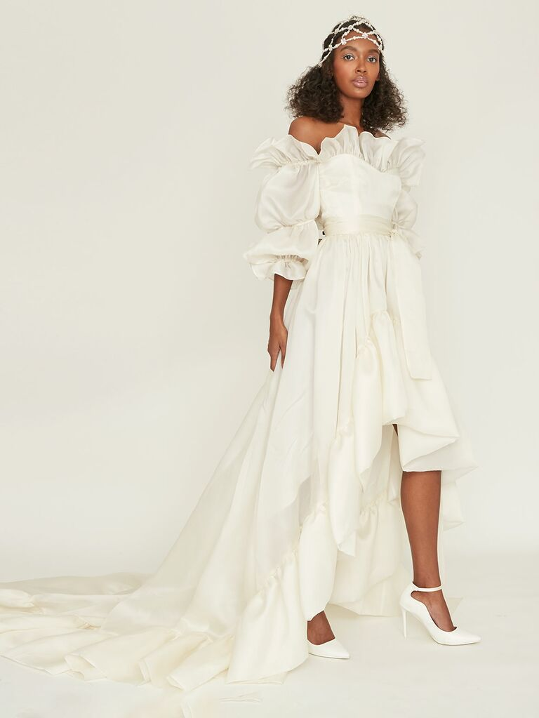 off-the-shoulder high-low wedding dress with puff sleeves and ruffles.