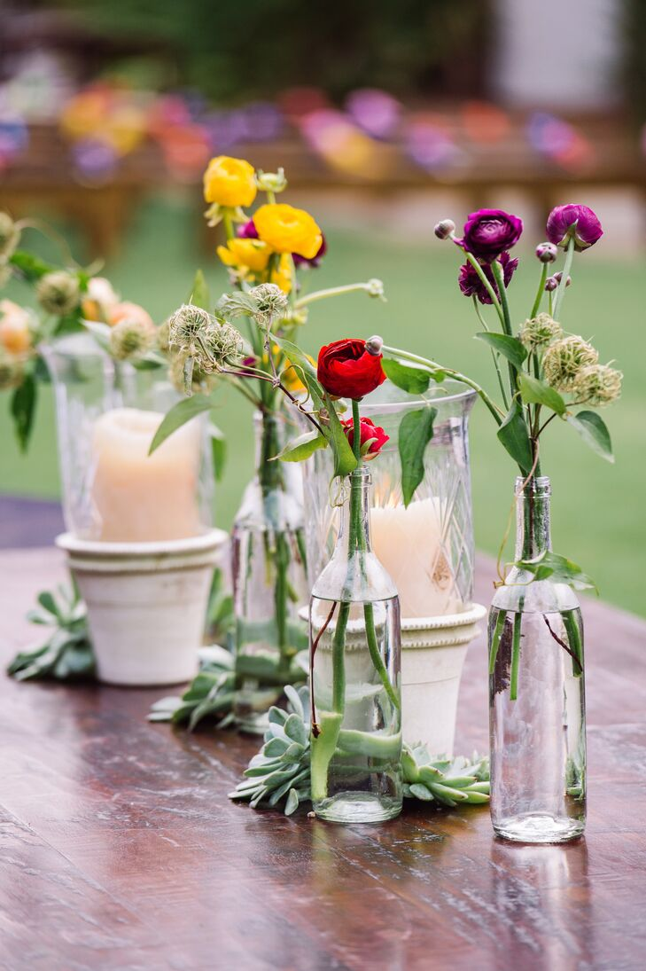 Even though it was raining throughout the day, the couple and their guests were still able to enjoy an outdoor cocktail hour. Some of the wooden tables were lined with candlelights inside vintage planters and clear glass bottles filled with bright ranunculus. Succulents also lined the center of the table.
