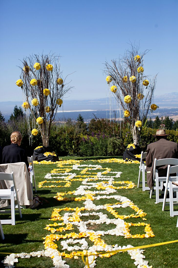 The couple exchanged vows overlooking San Francisco Bay. Yellow pomanders hung from trees defining the altar.
