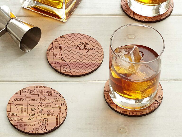 Wood coasters engraved with different city grids alongside glasses of whiskey