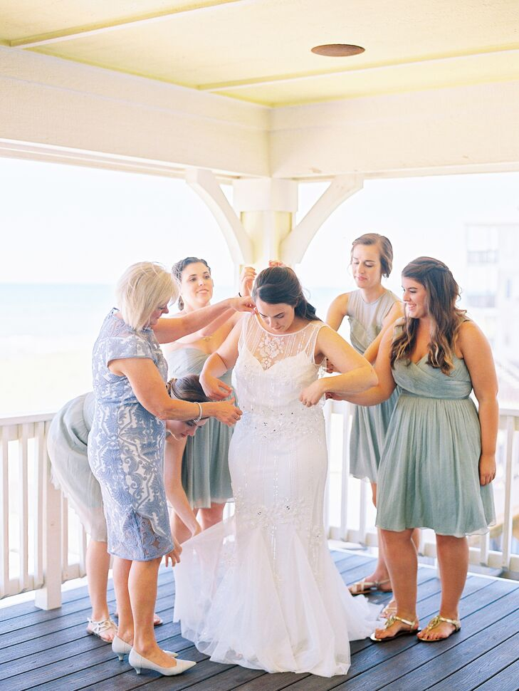 With a beach ceremony, Taylor knew she wanted her dress to really flow. But she also wanted lots of beaded detailing for some sparkle. The Magnolia gown from BHLDN was exactly what she wanted with an illusion neckline, blouson waist and layered tulle skirt.