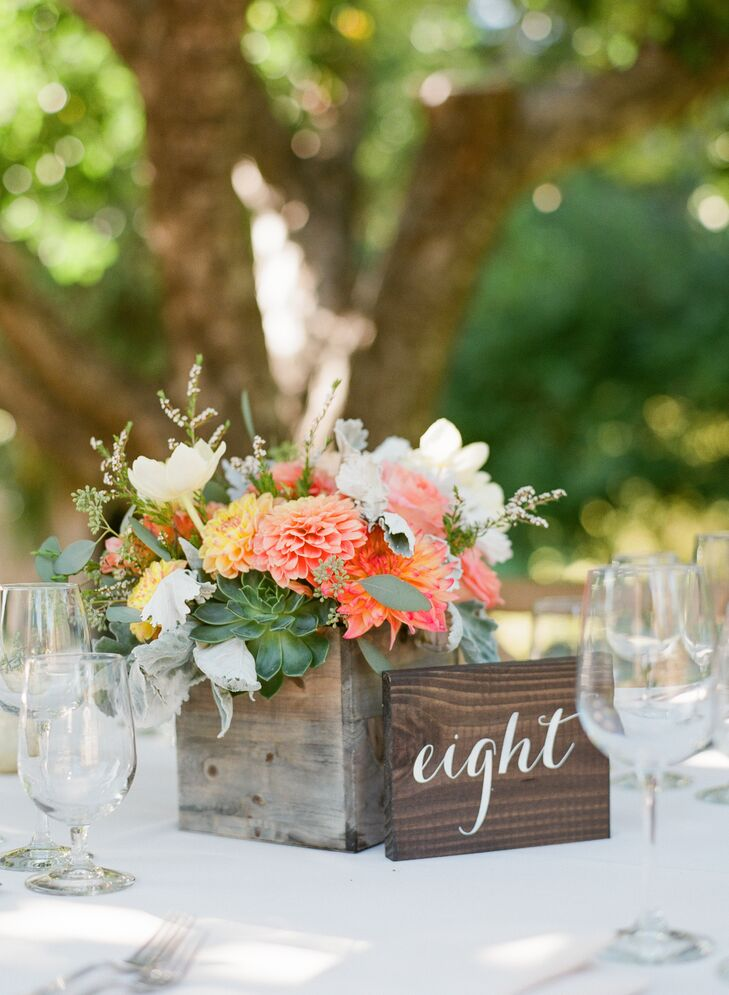 Each dining table at the reception had slabs of wood with numbers written in white. Pink dahlias, roses and several other blooms filled wooden boxes, which served as rustic centerpieces.