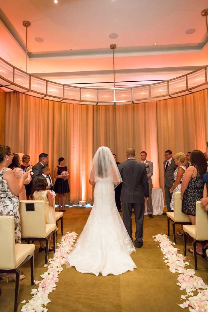 White and pink flower petals lined the aisle at the indoor reception as the room was illuminated with blush pink lighting.