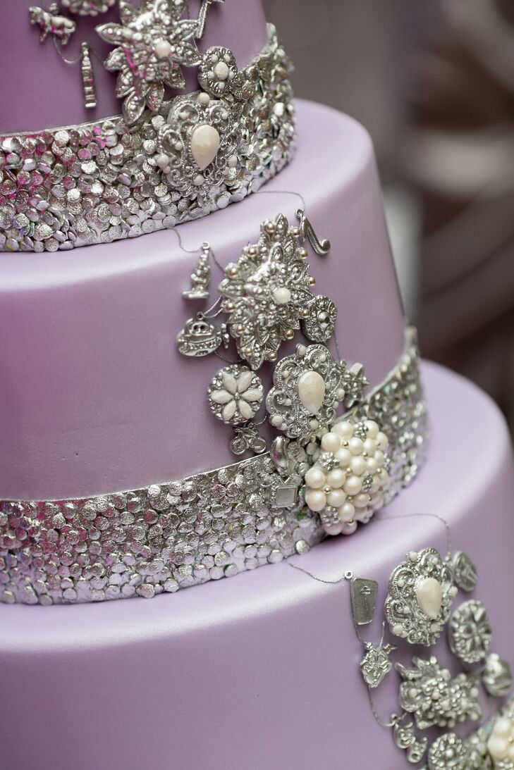 The three-tier wedding cake fit the color scheme and style of the reception and had a silver charm bracelet design draped along the side. Each charm was a meaningful symbol of the couple's hobbies.