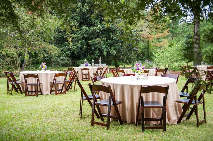 The reception decor featured neutral tablecloths, wooden folding chairs and purple floral arrangements.
