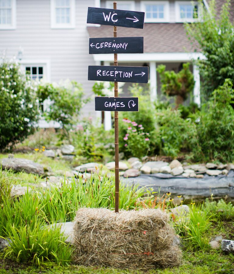 A cute rustic sign shows guests the way at a barn wedding