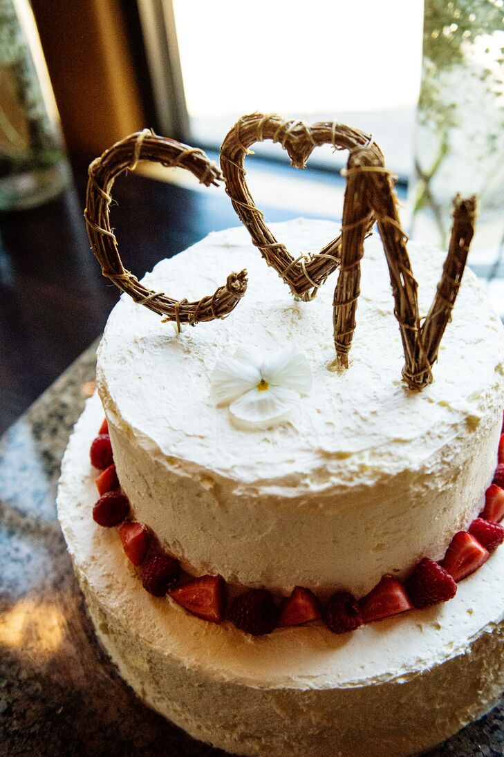 For dessert, Crystal and Nathan enjoyed a two-tier white buttercream wedding cake. The bottom layer was topped with fresh strawberries for a little added freshness. The top of the cake was topped with twigs formed to create the initials for the couple with a heart in the center.