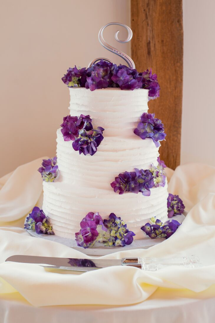 """Dice's Creative Cakes baked a three-tier white confection for the couple that complemented their whimsical centerpieces. Once again putting a fun twist on their formal wedding, Sarah and Matt had purple hydrangeas placed on each tier and topped the dessert with a fun silver """"S."""" """"Speaking of cakes, as a surprise for Matt I had a groom's cake made in the shape of an Xbox, which he enjoys playing in his free time,"""" Sarah says."""
