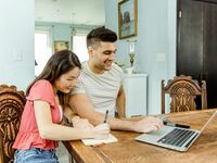 Engaged couple planning on laptop at home