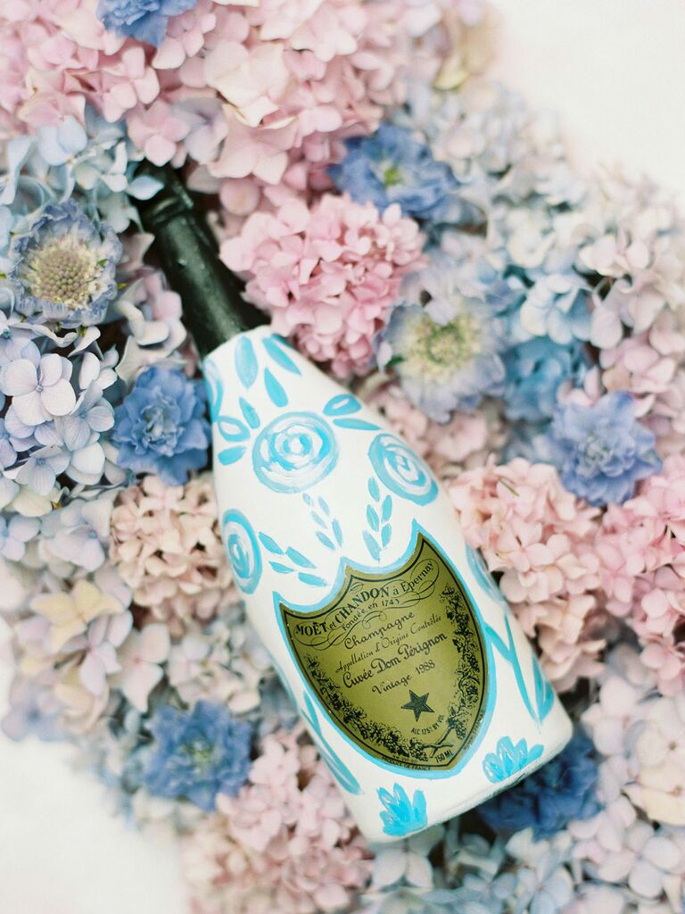 Blue and white bottle of champagne on bed of pastel flowers