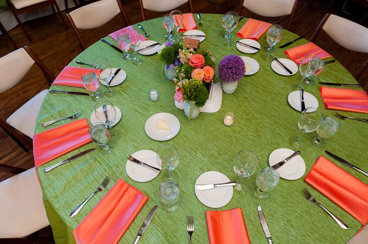 Katie and Haydn decorated their reception tables with green and orange linens and purple, green and orange floral arrangements.