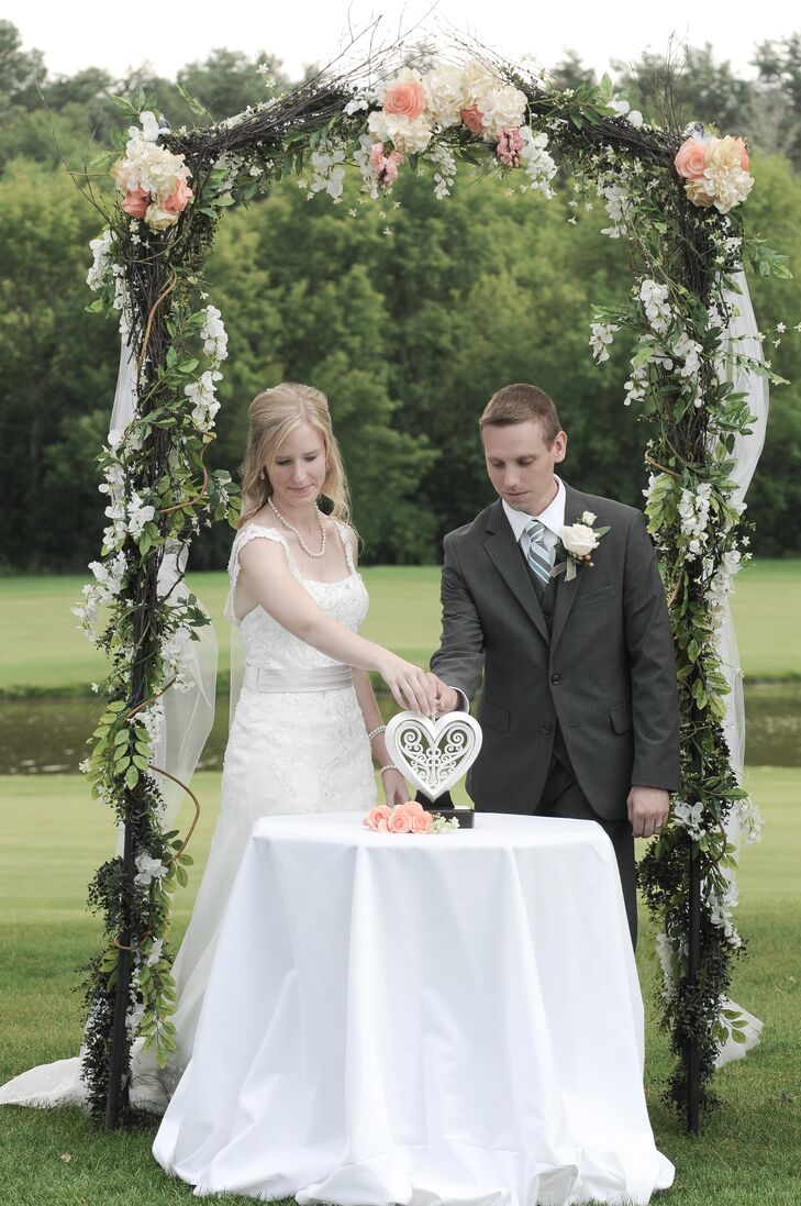 Amy and David said their vows under a flower-strewn arch, and opted for a less traditional unity ceremony by placing together a white, wooden, unity heart. The outer heart represents the husband, inner heart the wife and the gemstone core represents god, who binds them together.