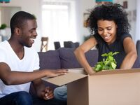 Couple opening a box and taking out a plant