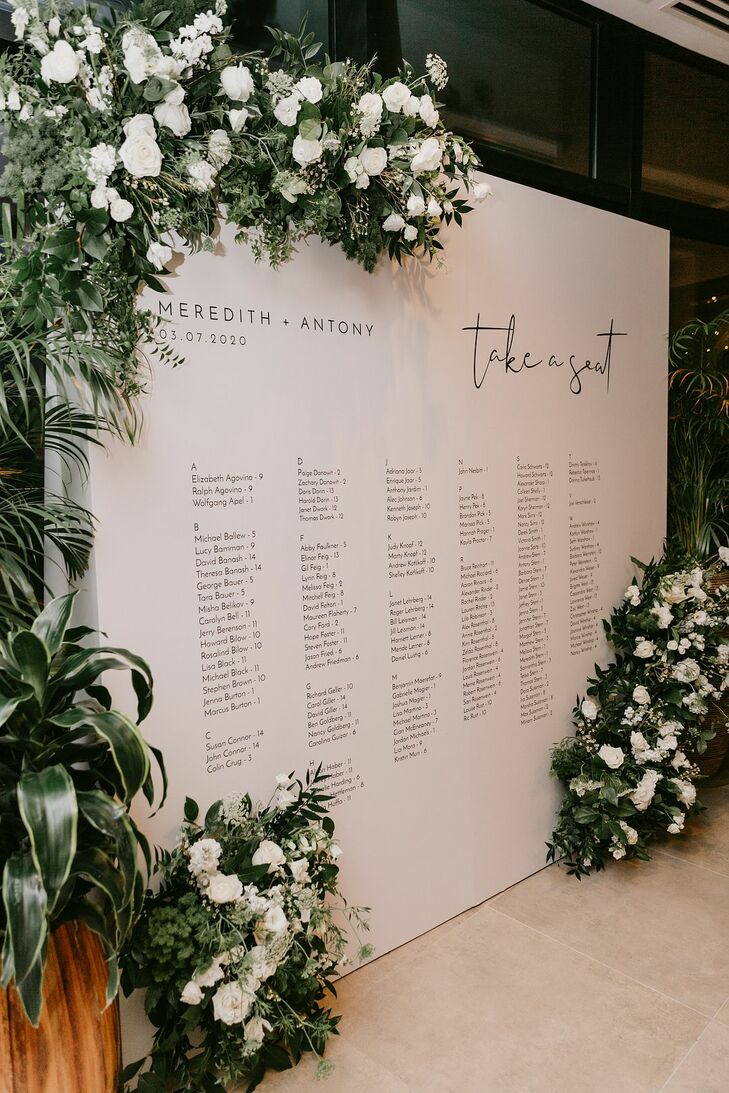 Modern Wall-Mounted Seating Chart with Greenery and White Roses