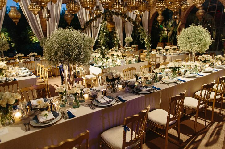 """Fresh bundles of baby's breath piled high atop hurricane vases and full white roses displayed in blue and white ceramic bowls worked with the reception's lantern canopy and votive candles to achieve a whimsical, midsummer night feel. """"The venue was adjacent to a stunning rose garden, and we wanted to give guests the sense that the roses were freshly picked from the garden for our wedding,"""" Lauren says."""