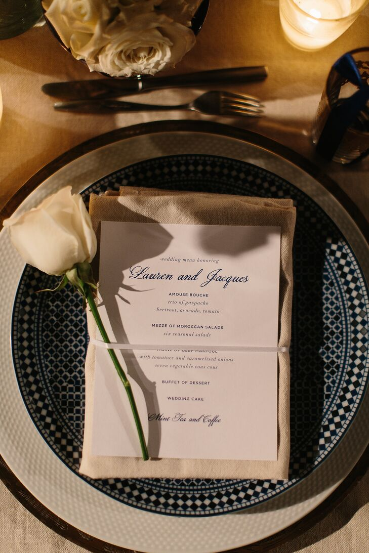 Place settings consisted of gold chargers, textured white china and blue fez-print starter plates and simple silverware. Gold-rimmed glassware gave the tablescapes an element of warmth, while the placement of a single white rose on each place setting infused the tablescapes with romance and charm.