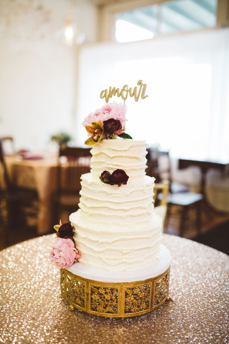 "Morgan and Stanley's wedding cake honored family traditions, incorporating flavors like red velvet, carrot and apple butter for each layer of the cake's three tiers. The decadent confection was iced in ivory buttercream and finished with pink peonies, burgundy roses and a vintage gold-tipped topper spelling ""amour,"" a nod to Stanley's Haitian roots."