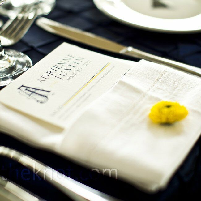 The monogrammed menu cards were tucked into white hemstitch napkins, accented by a single yellow flower at each setting.