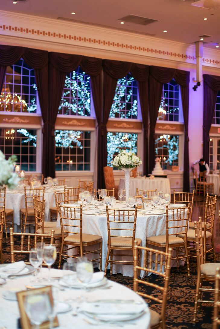 The ballroom reception featured purple uplighting and a view of illuminated trees outside. Tables were arranged with simple white tablecloths and gold chiavari chairs.