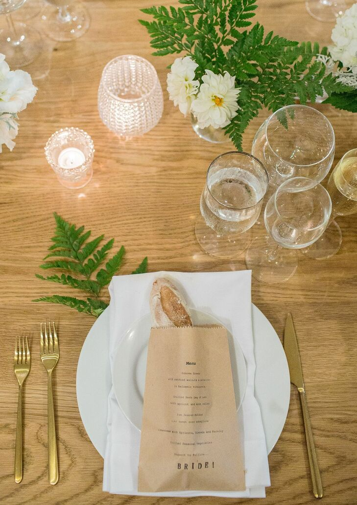 Wood dining tables were simply set with white dinnerware. The menu was printed on a brown paper bag containing a baguette at each seat setting.