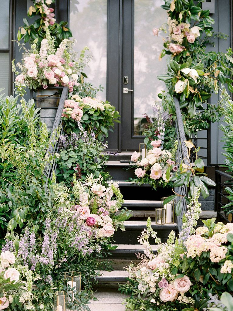 Stoop decorated with lush wedding flowers and candles