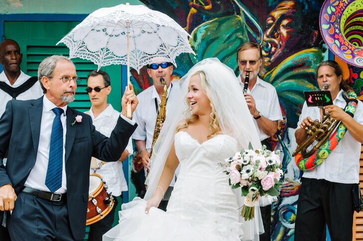"""Lona's father escorted her to the ceremony from a block away, accompanied by a New Orleans' style band, all while holding a white parasol over her head, a twist on an old Italian tradition. """"Our musical entrance was a complete surprise to our guests and to Bryan,"""" she says."""