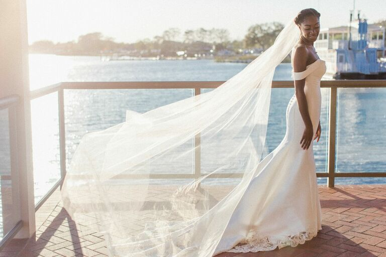 Bride wearing off-the-shoulder dress with veil flowing in the wind