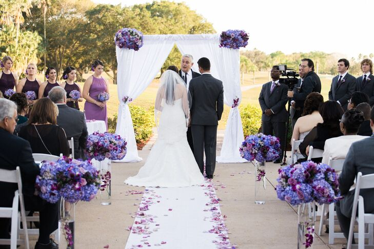 Cassandra, Josh and their florist,  Beautiful Kreations, went all out on the ceremony decor. Bunches of blue hydrangeas, purple calla lilies and purple roses were placed atop the couple's wedding arch while similar blooms topped floating pink cymbidium orchids in cylinder vases along the aisle. For an added purple touch, flower petals in the same hues accented their white aisle runner.