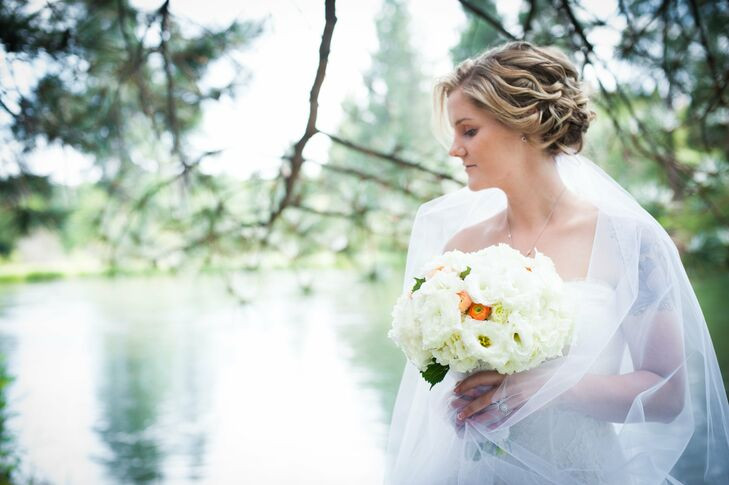 Nicole's bridal look featured a soft, curled updo, a handmade veil, and a white bouquet with pops of coral.