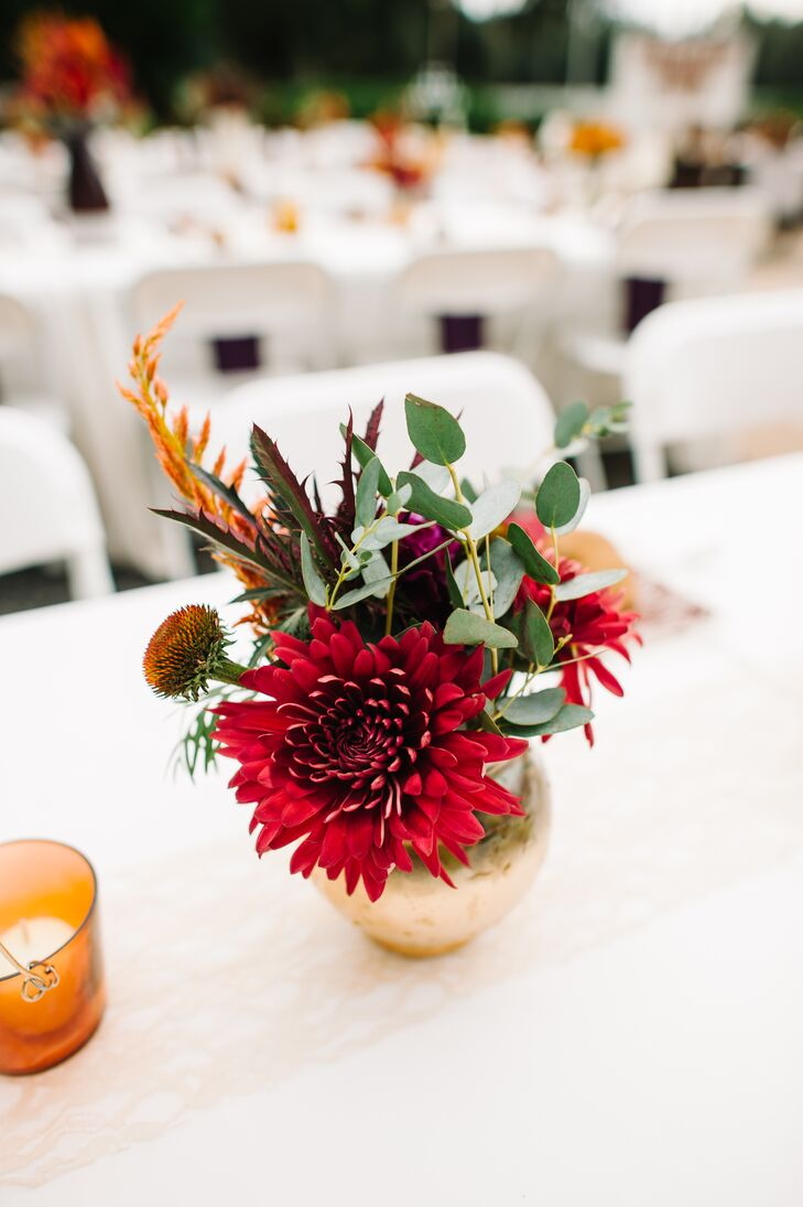 Every arrangement on Shelby and Zack's tablescapes was a little different. 2Birds Events  filled the low gold and tall plum vases with a mix of red, green and burgundy hues to make it feel even more like fall. A specific centerpiece had red dahlias, eucalyptus, scabiosa and leaves.